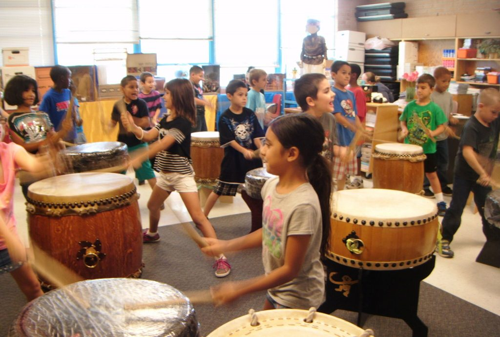 Kids learning taiko in the classroom